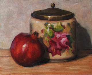 Oil painting of a pomegranate beside an antique biscuit barrel with a flower pattern.
