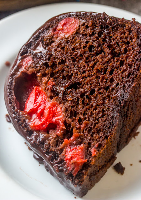slice of chocolate bundt cake studded with cherries on plate