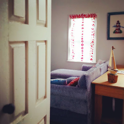 View through the door of a one-twelfth scale modern miniature house, into the lounge where you can see a grey velvet sofa underneath a window with a red and white net curtain at it. Behind the sofa is a wooden sideboard with a model sailboat on it. And above it is a corss stitch picture of a lighthouse.