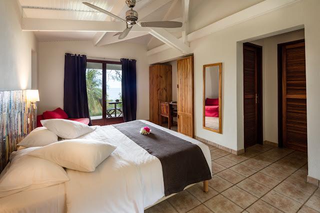 Chambre avec vue sur la mer et décoration florale sur le lit