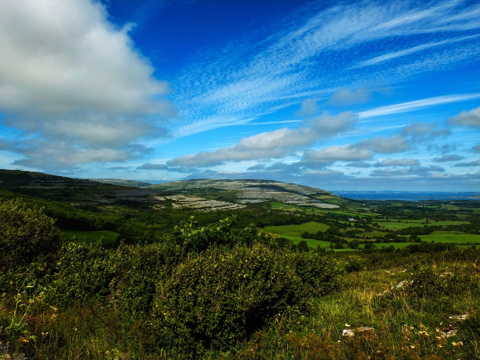 Landscape of the Burren area in Co.Clare on a sunny, blue sky day with clouds.
