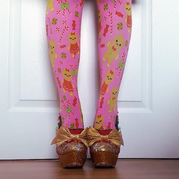 front view of legs in pink gingerbread man tights with gold glitter and bow platform shoes