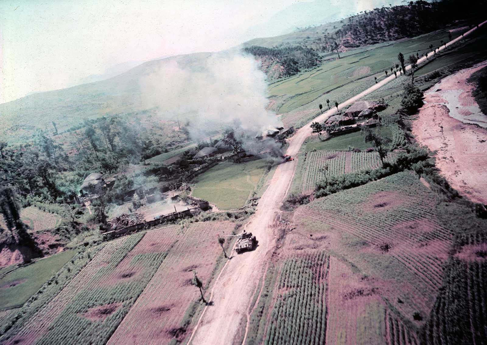 This picture was taken by a USAF RF-80 photo reconnaissance plane of actual strafing attacks by 5th Air Force planes on North Korean targets. This shows a small village housing North Korean vehicles and troops. Burning jeep in the background and a T-3V Tank.