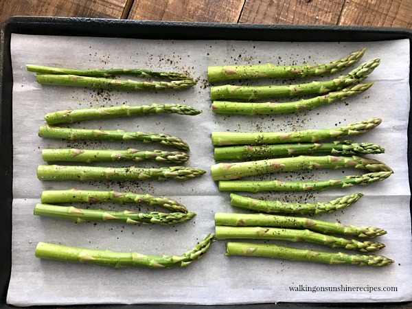 Place asparagus on a parchment lined baking tray from Walking on Sunshine