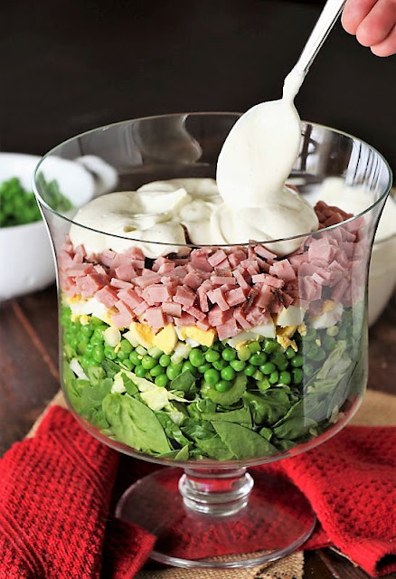 Spooning Creamy Ranch Dressing on Top of Layered Spinach Salad Image