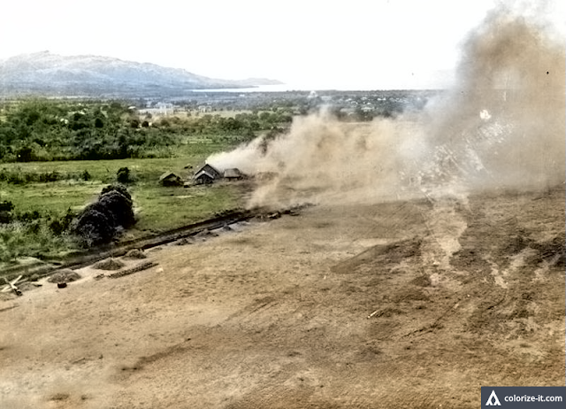 Photo of the Batangas airdrome under attack by American planes in 1945.  Image source:  United States National Archives.  Colorized courtesy of Algorithmia.