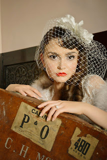 Girl with, Veronica Lake, inspired hair accessorised with a birdcage veil and 1940's style makeup