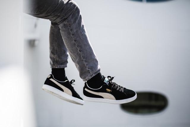 all black puma suede on feet