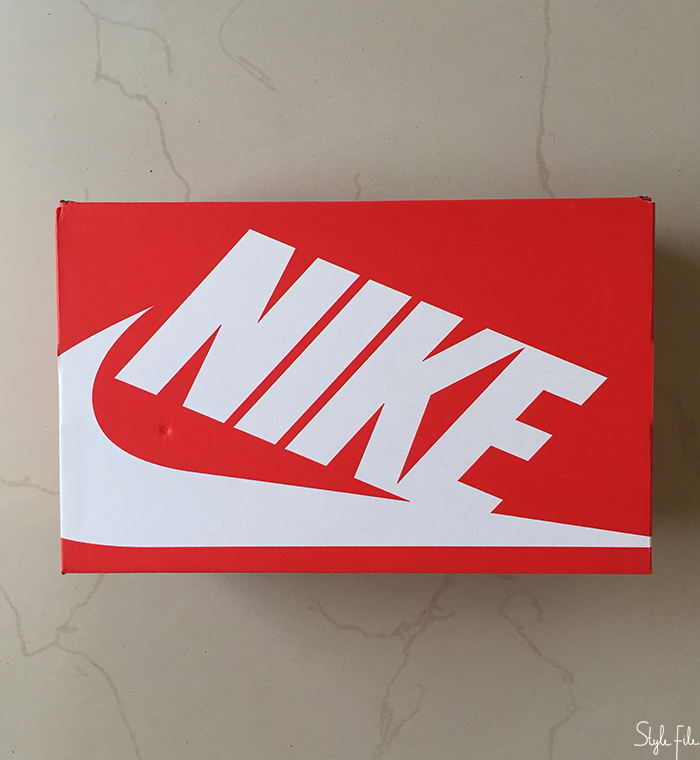 Image of a red cardboard nike box on a beige background with the nike brand and swoosh in white