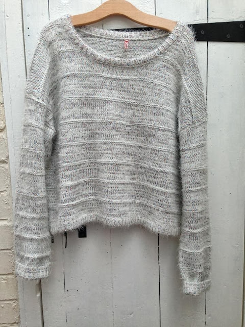 full shot of the white fluffy jumper with hints of rainbow thread running throughout