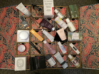 A photo of the contents of all of the Liberty London Beauty Advent calendar on top of the calendar