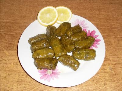 Πιάτο με ντολμαδάκια τυλιγμένα σε αμπελόφυλλα και δυο φετες λεμόνι για ντεκόρ
