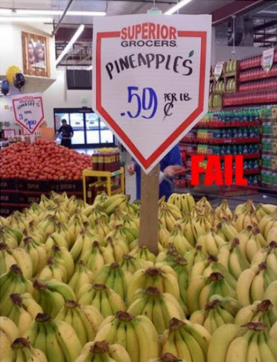 Photo of Superior Grocers sign, ad for Pineapples in a pile of Bananas. Fail. The Atheist Nightmare. marchmatron.com