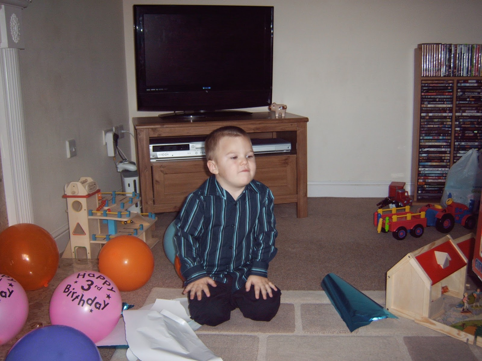 Ben on his 3rd birthday kneeling on the floor surrounded by presents and balloons