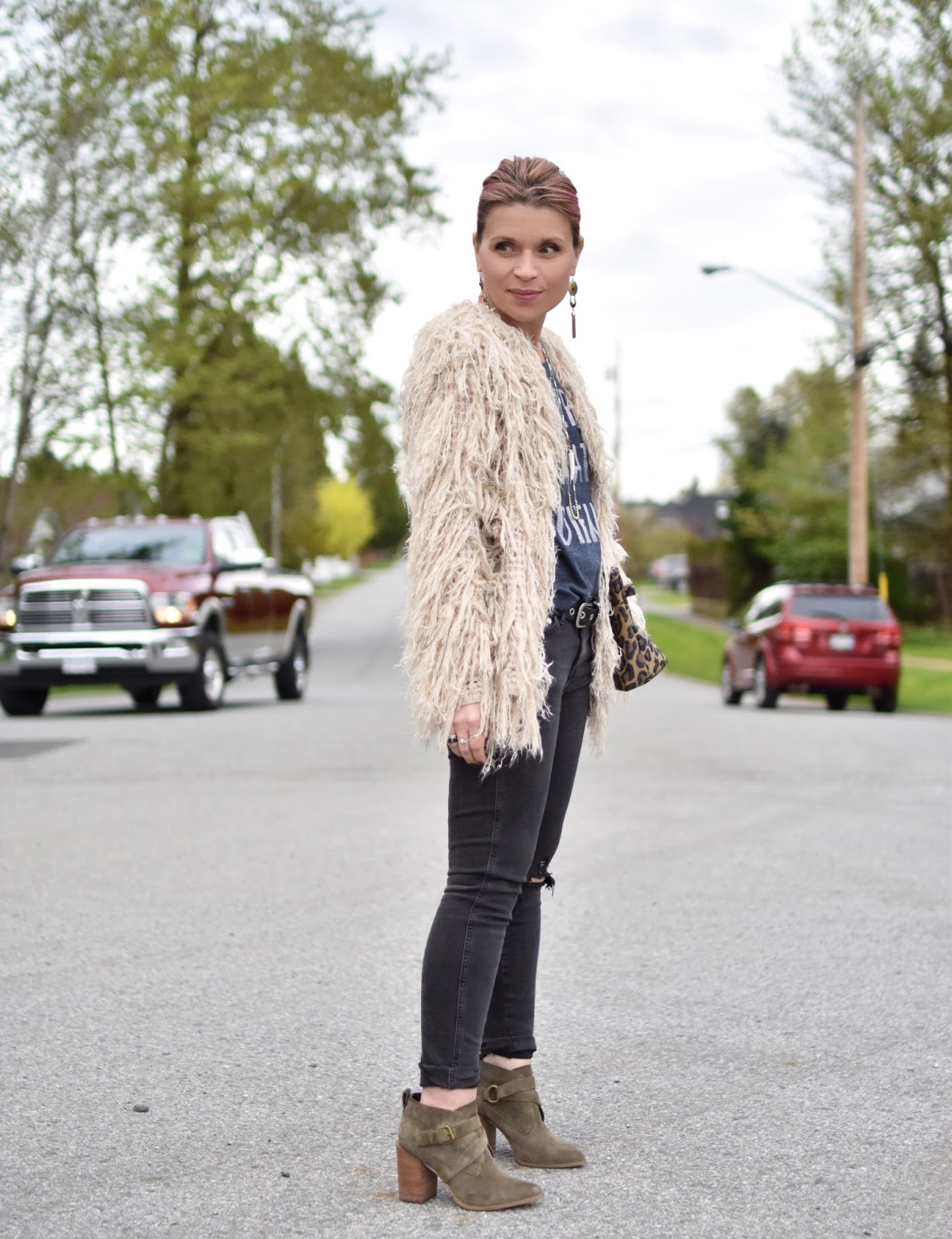 Monika Faulkner outfit inspiration - styling distressed black skinny jeans with a graphic tee, shaggy cardigan, and olive suede booties