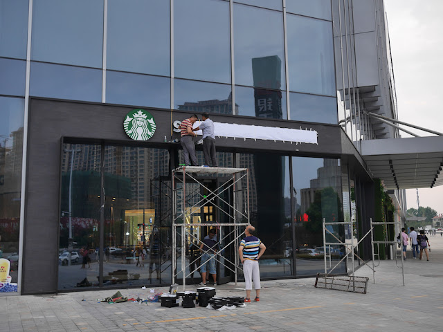 workers putting up lettes for a Starbucks storefront sign in Bengbu