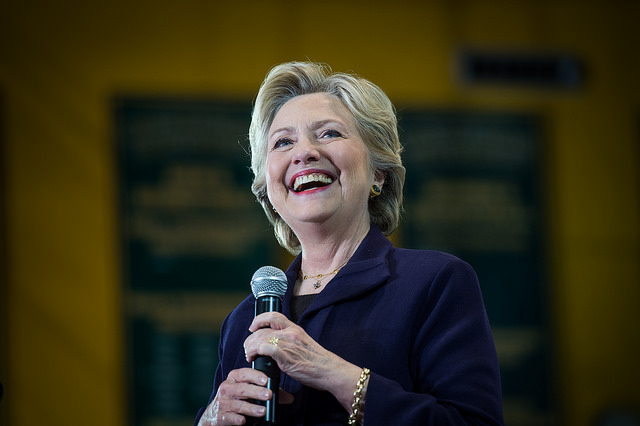 image of Hillary Clinton standing onstage, holding a microphone and smiling broadly