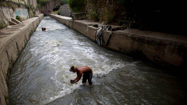 Venezolanos pobres recurren a buscar chatarra en un río