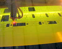 laser cutting the design, viewed through heavily tinted filter