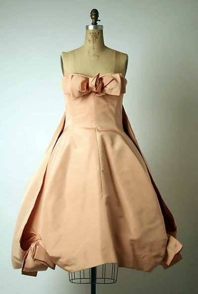 Light rose short evening dress with bows at hemline by Yves Saint Laurent for House of Dior Spring/Summer 1958 displayed on dress form