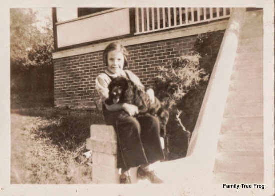 little girl dressed in overalls sitting on step with black spaniel