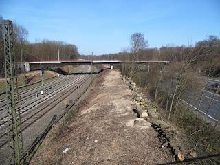 Eine Brücke, darunter verlaufen Bahngleise und eine Autobahn