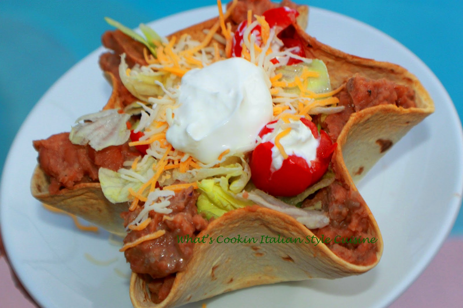 these are homemade taco shells filled with a salad with refried beans, salad, cheese, lettuce and tomato