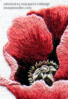 Close-up of thread paintined red poppy centre