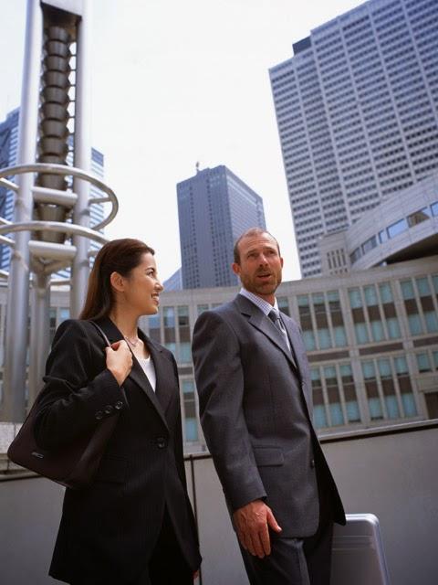 Se observan una mujer y un hombre en traje en el exterior cerca de unos grandes edificios
