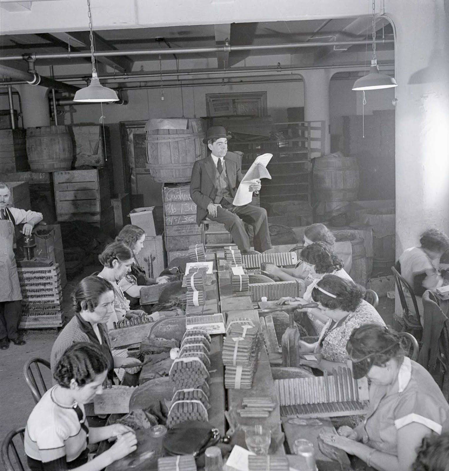 A lector reads a newspaper to workers in a cigar factory. 1900s.