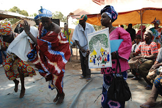 Women from Tankanto Maoundé dance with the image Tostan uses to represent the right to peace and security.