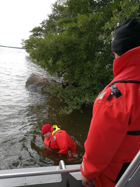Henkilö pelastautumispuvussaan vedessä. Toinen seisoo veneessä.
