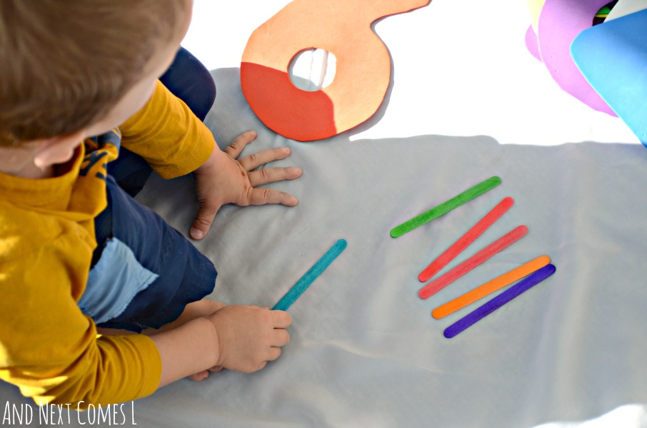 Preschooler counting craft sticks from And Next Comes L