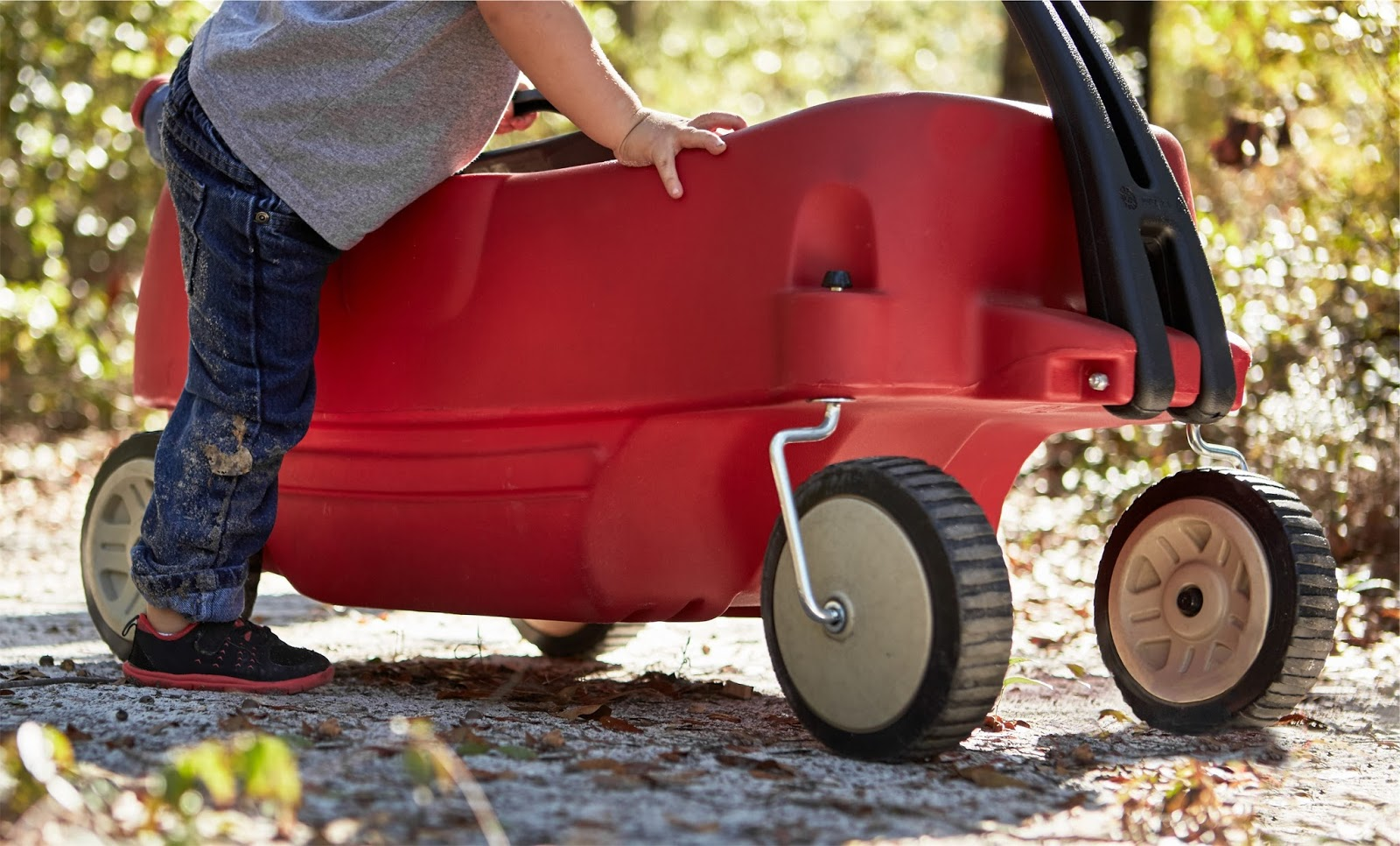 Little boy about to climb into a play wagon - child backless booster car seats new rules 2016 - motherdistracted.co.uk