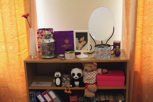 a bookshelf made out of pine wood, full of trinkets, a mirror, jewellery boxes, flowers, candles, a lantern, and some stuffed toys