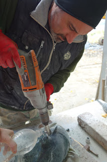 Quarryman Marco Nardini uses a diamond drill to core a hole in marble.