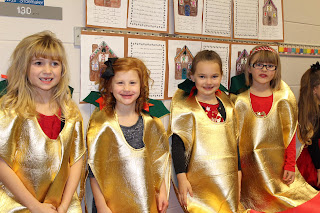 Four girls smiling wearing gold costumes