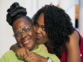 A black teen hugs her mother who is smiling
