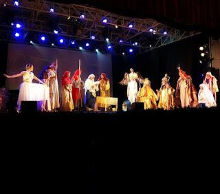 Elenco do Auto de Natal de Canela cantando no palco.