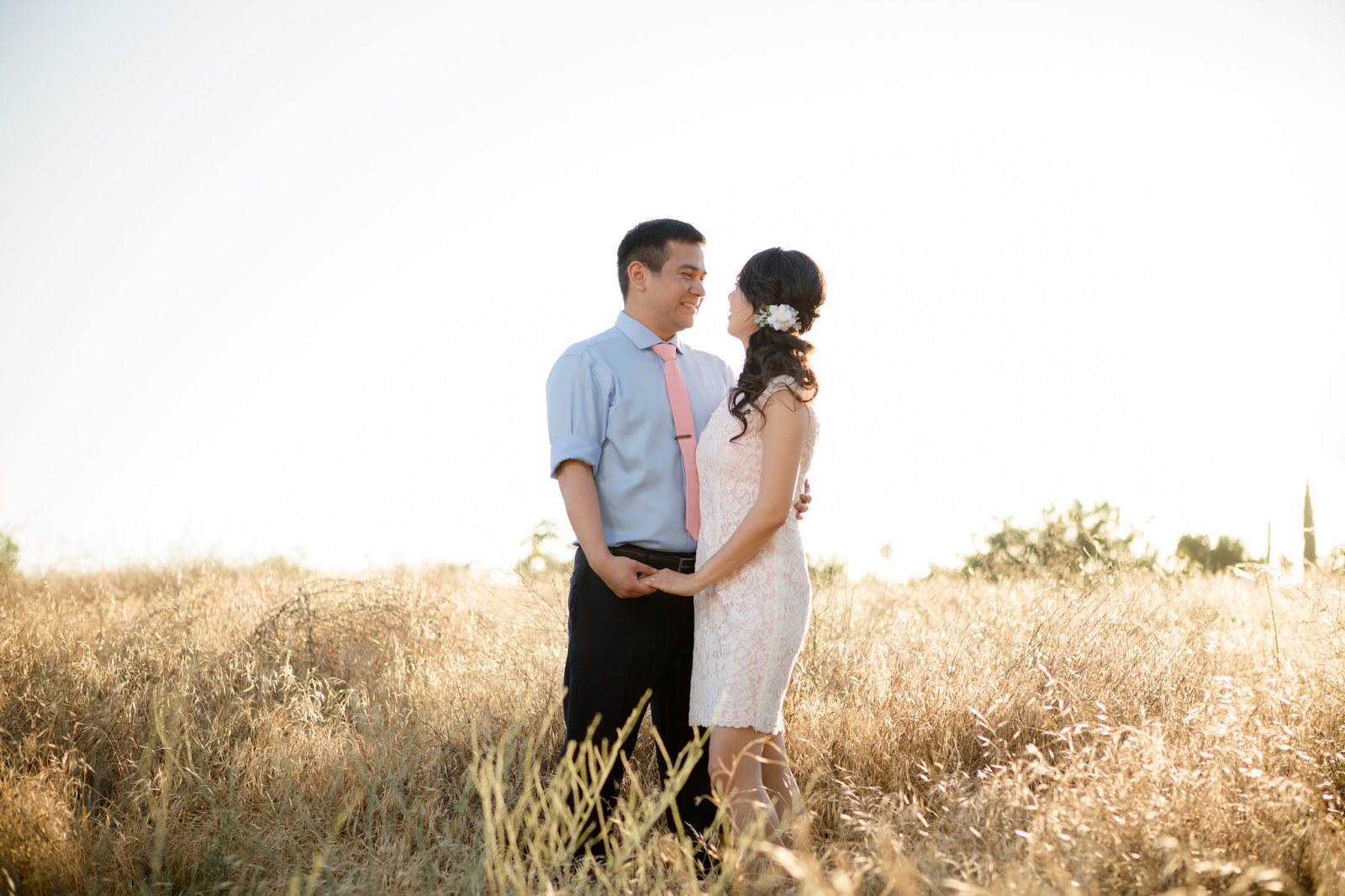 bride and groom standing in a field looking at each other
