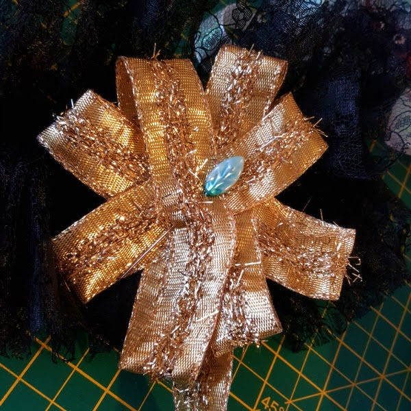 gold wired ribbon pinned into a rosette shape on the black lace cuff