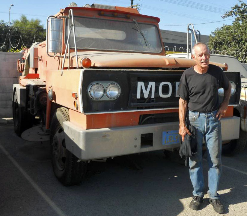 Man in front of street sweeper.
