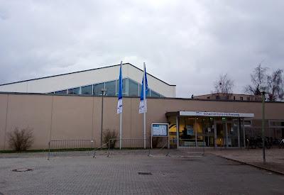 Abbildung der Schwimmhalle Hüttenweg von der Eingangsseite. Zwei Fahnen der Berliner Bäder Betriebe. Gut zu erkennen ist die erhöhte Hallendecke unter der das Drei-Meter-Brett liegt.