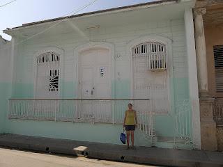 Hellgrünes Haus, hohe Fenster mit geschlossenen weißen Läden, davor Metallgitter, ebenfalls weiß gestrichen.