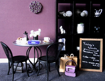 Modern one-twelfth scale miniature cafe in colours or purple, white and black. A table is set for coffee and there's a handbag and shopping on the floor next to one of the chairs.