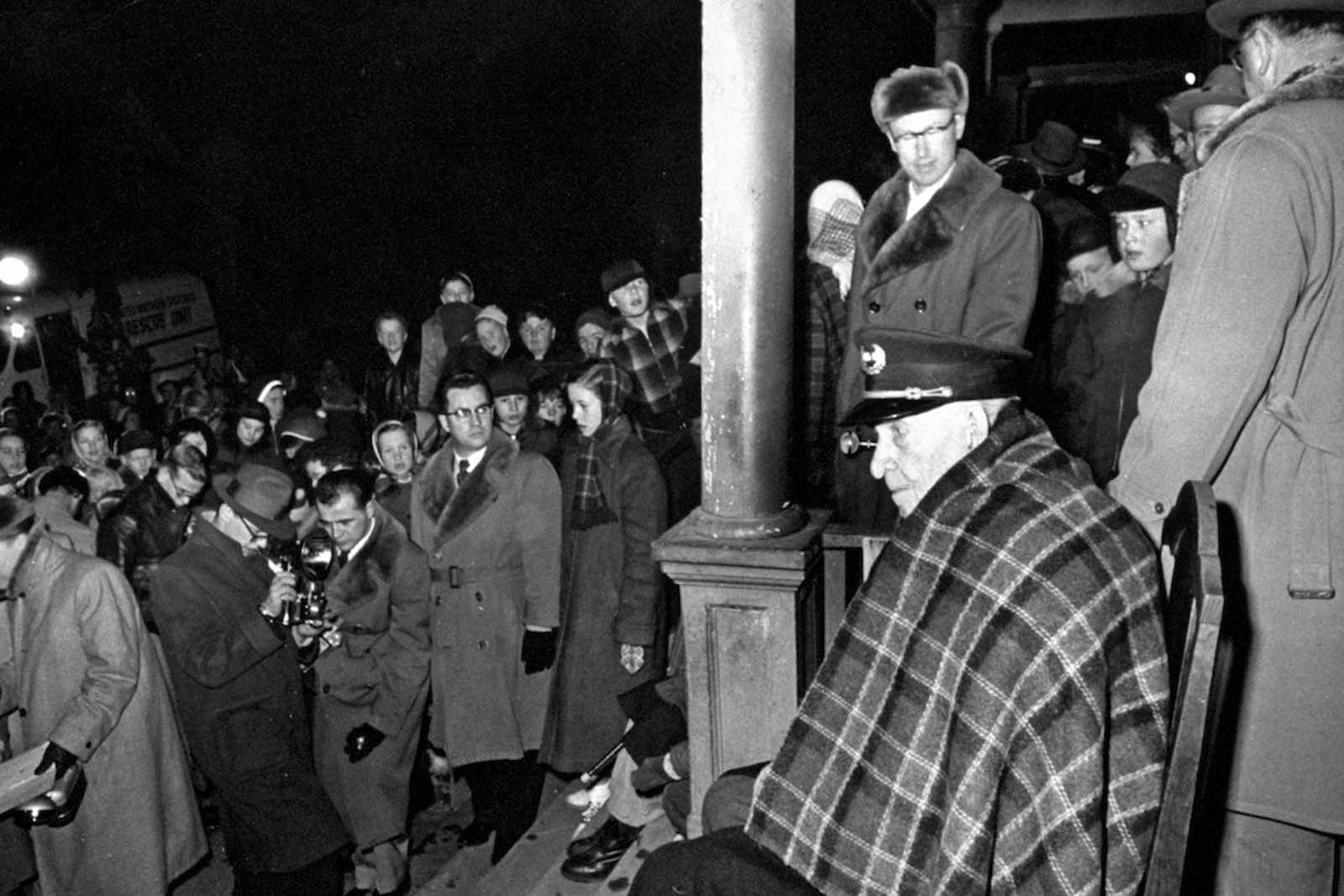107 years old last remaining Grand Army of the Republic (GAR) Civil War Veteran Albert Woolson (seated) sitting in the front porch wearing a military hat and blanket while people and photographers are passing by. 1954.
