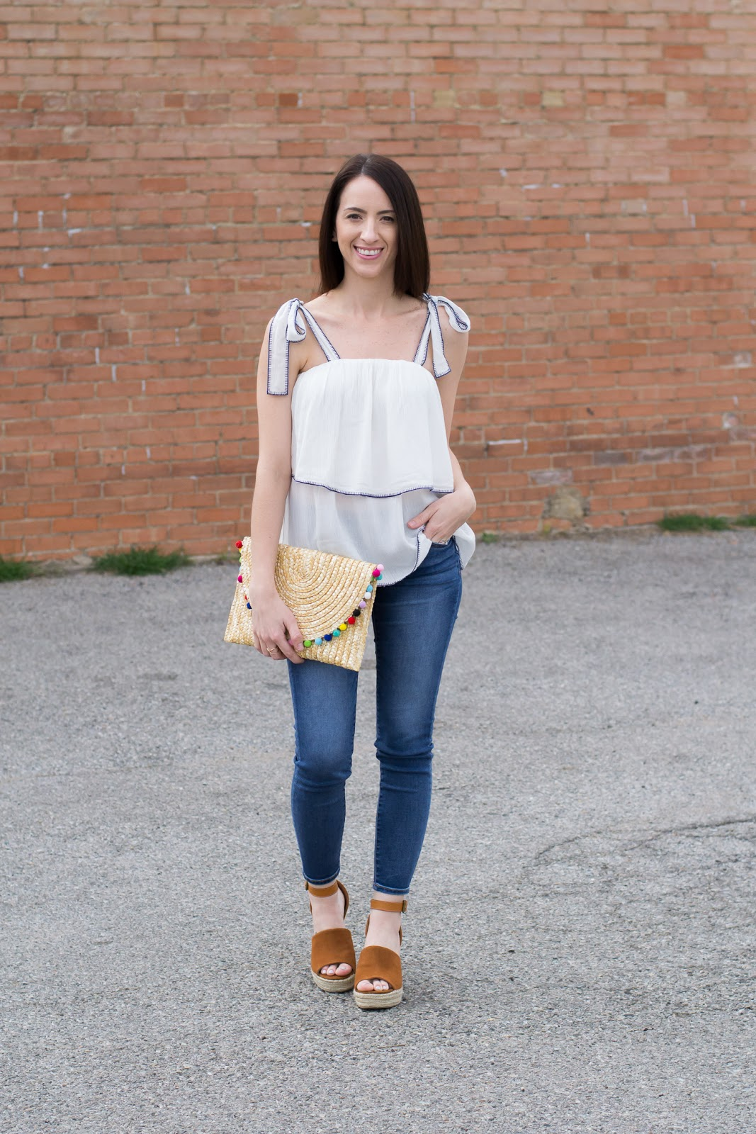 White ruffle top with bow ties and straw clutch