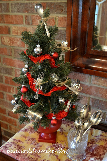 mini christmas tree with baby spoons and red ribbon