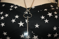 a close up of a bustier of a star print dress, with a silver key pendant on top