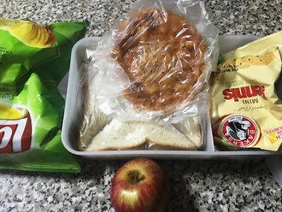 Lunch-box with Dr Oetker mini-pizza, apple, mini tennis biscuits and potato crisps Lays